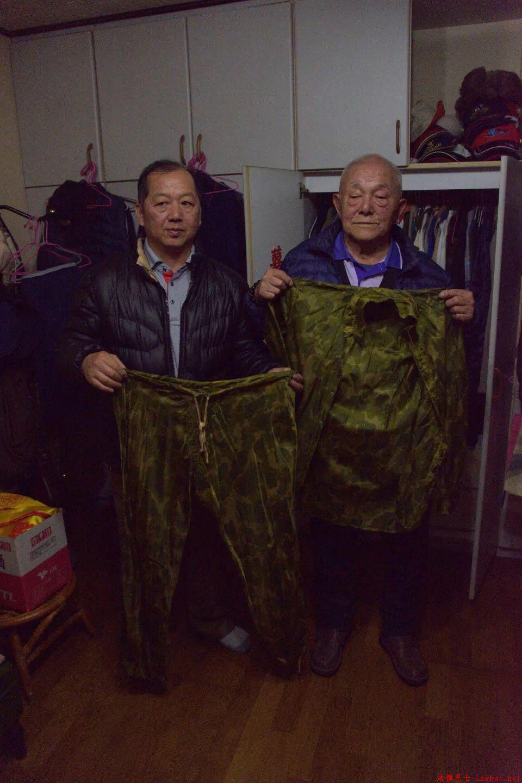 李云棠(右)展示当年女村民为他用降落伞做的衣服.jpg